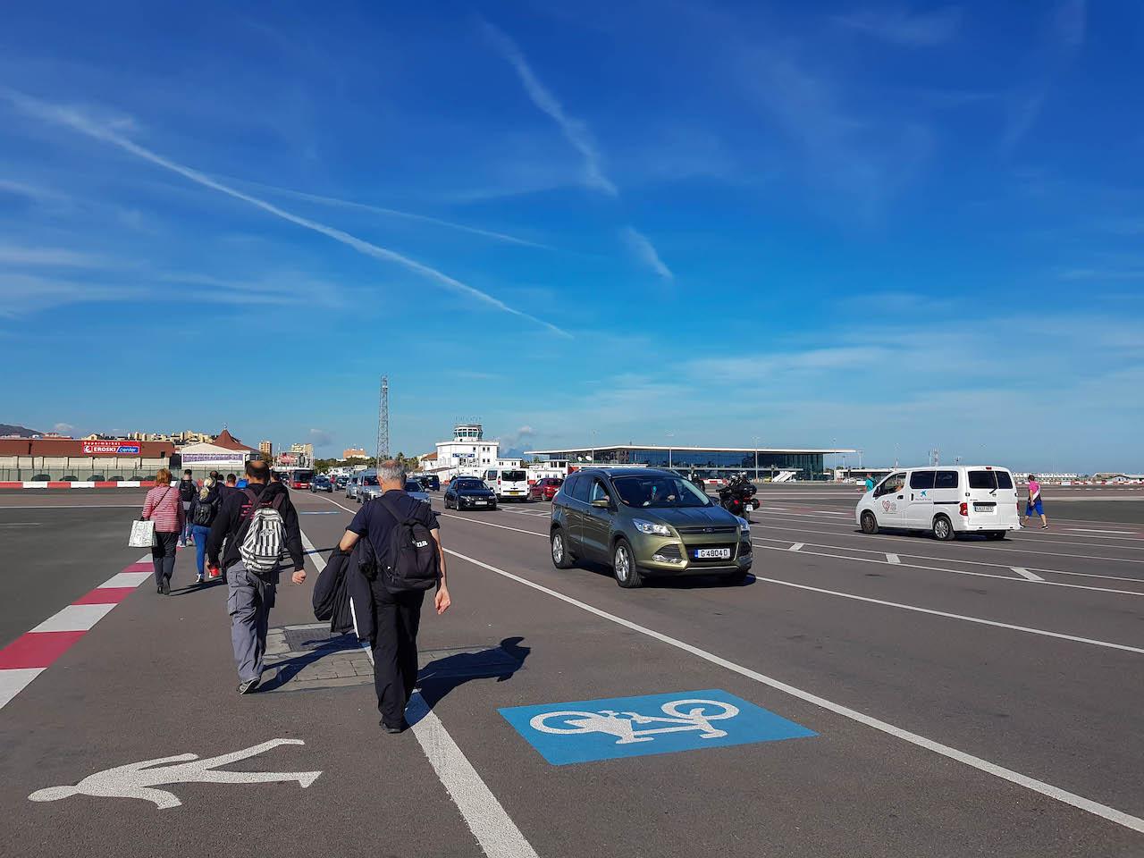 Leute laufen über die Rollbahn in Gibraltar.