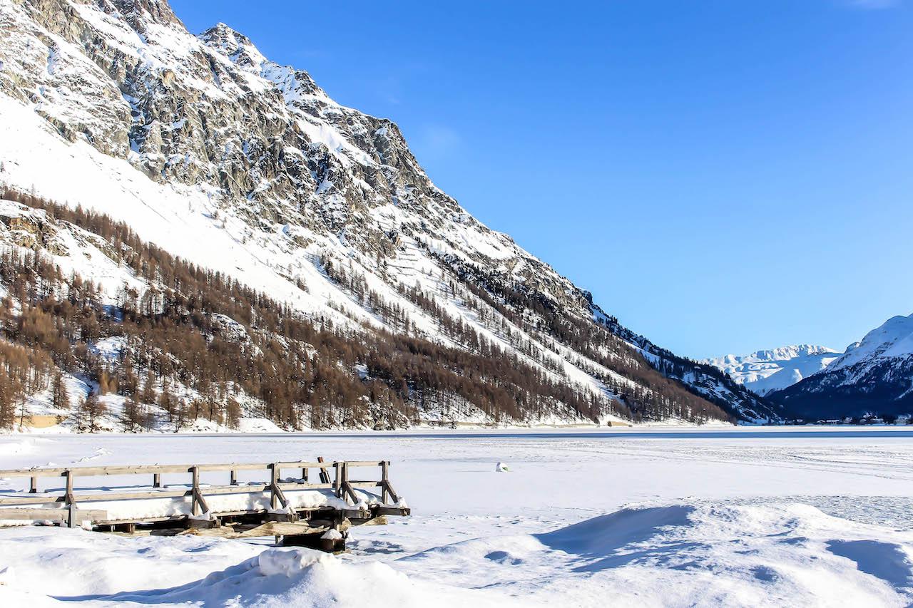 Steg mit Schnee bedeckt, der auf den See hinaus geht.