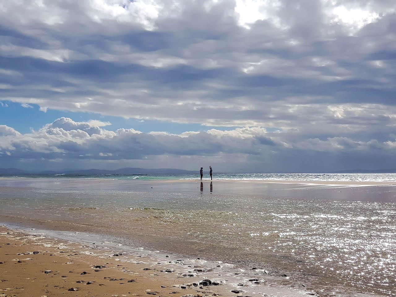 Zwei Personen stehen am Strand.
